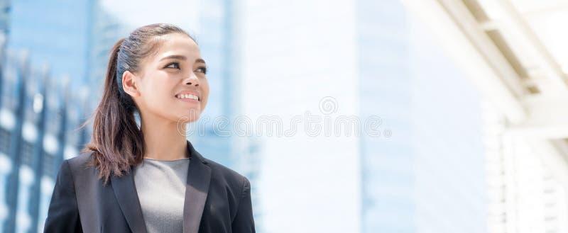 Усмехаясь молодая азиатская коммерсантка на предпосылке офисного здания нерезкости стоковая фотография