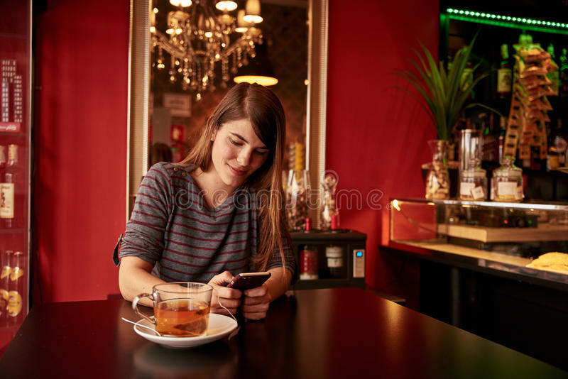Усмехаясь молодая дама сидя в баре стоковая фотография rf
