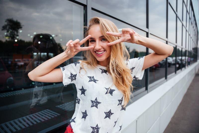 Усмехаясь молодая белокурая женщина показывая знак v пока стоящ outdoors стоковые изображения