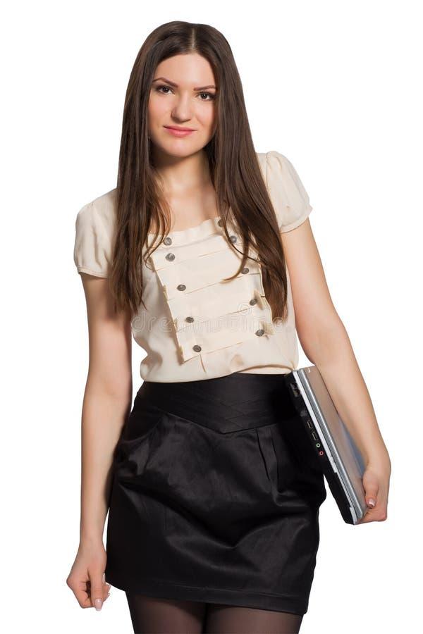 Усмехаясь молодая девушка студента с закрытой компьтер-книжкой на белой предпосылке стоковое фото