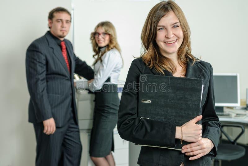 Усмехаясь молодая женщина в офисе стоковые фото