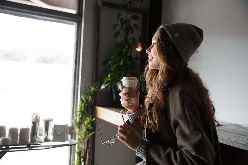 Усмехаясь молодая женщина держа стекла и выпивая кофе в кафе стоковое фото rf