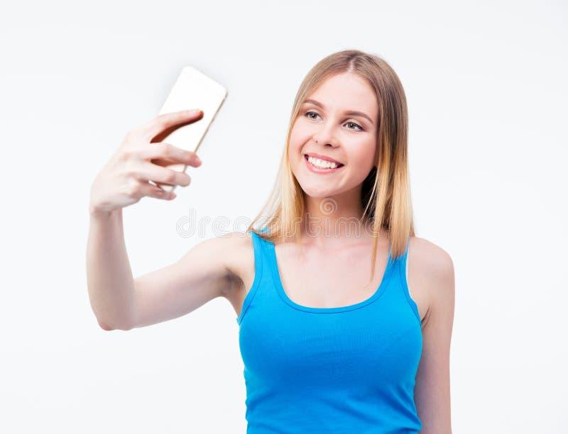 Усмехаясь молодая женщина делая фото на smartphone стоковое фото