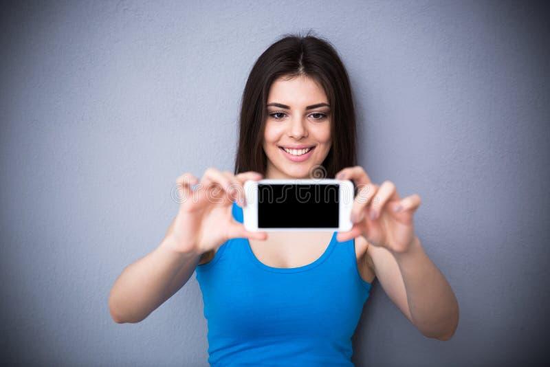 Усмехаясь молодая женщина делая фото selfie стоковое фото rf