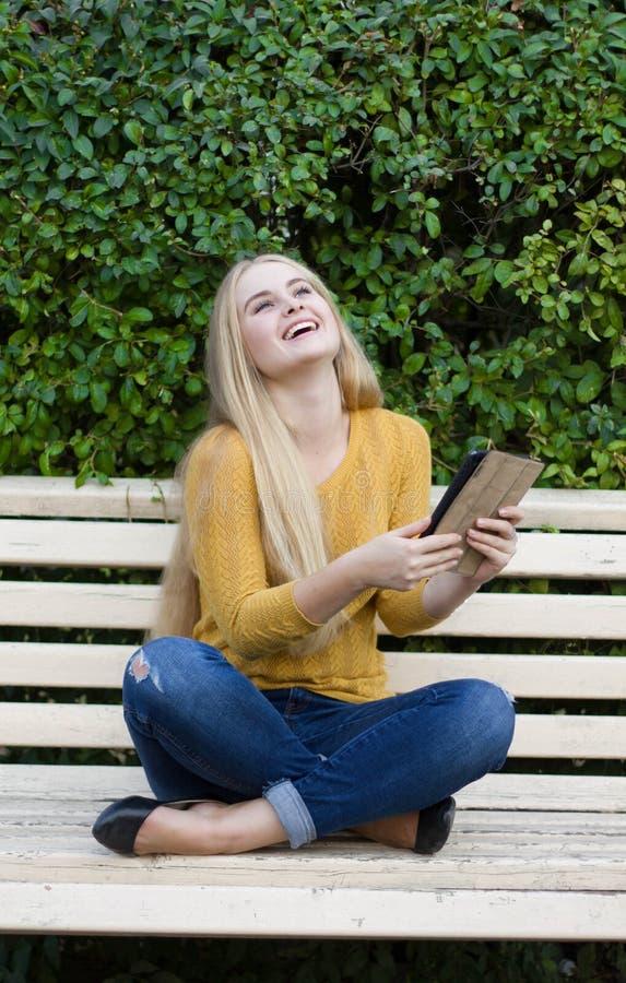 Усмехаясь молодая женщина или девушка с планшетом outdoors стоковые изображения rf
