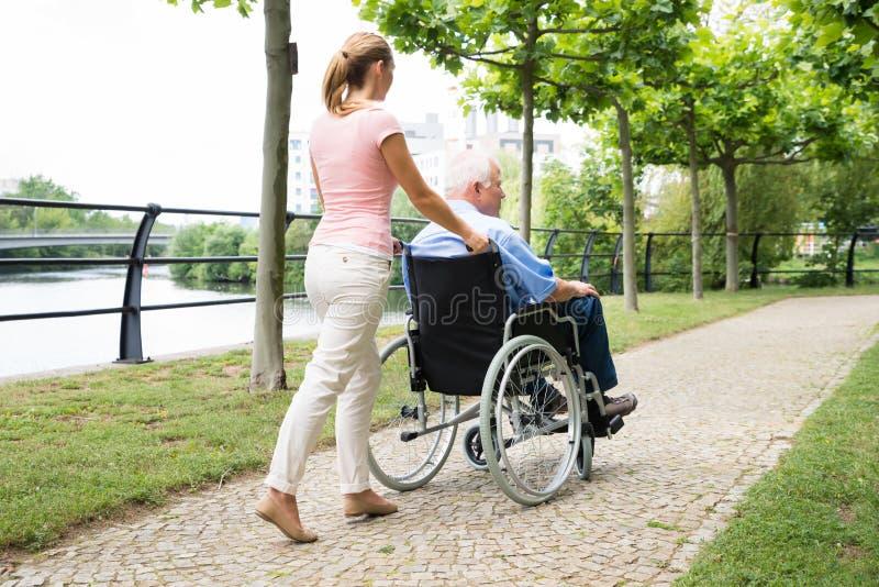 Усмехаясь молодая женщина помогая ее неработающему отцу на кресло-коляске стоковое фото