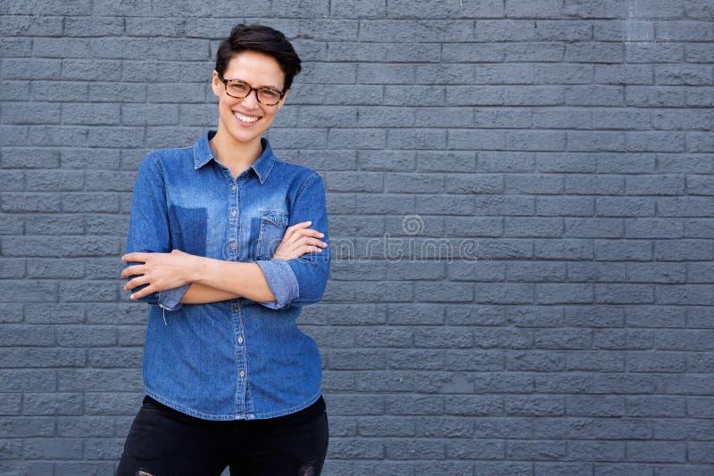 Усмехаясь молодая женщина представляя с стеклами против серой предпосылки стоковые фотографии rf