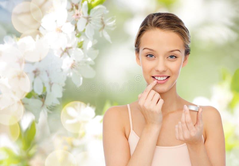 Усмехаясь молодая женщина прикладывая бальзам губы к ее губам стоковые изображения rf