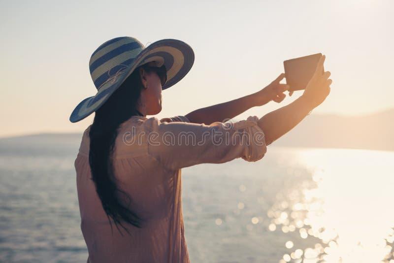 Усмехаясь молодая женщина принимает фото selfie морем стоковые фото
