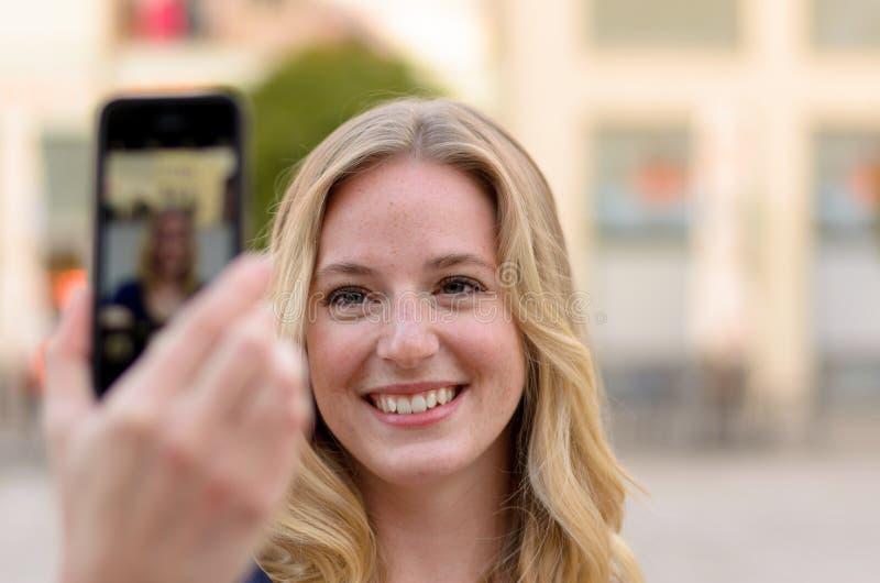 Усмехаясь молодая женщина принимая ей selfie стоковое изображение