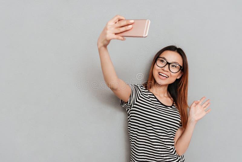 Усмехаясь молодая женщина разговаривая с друзьями телефоном и развевать стоковое изображение