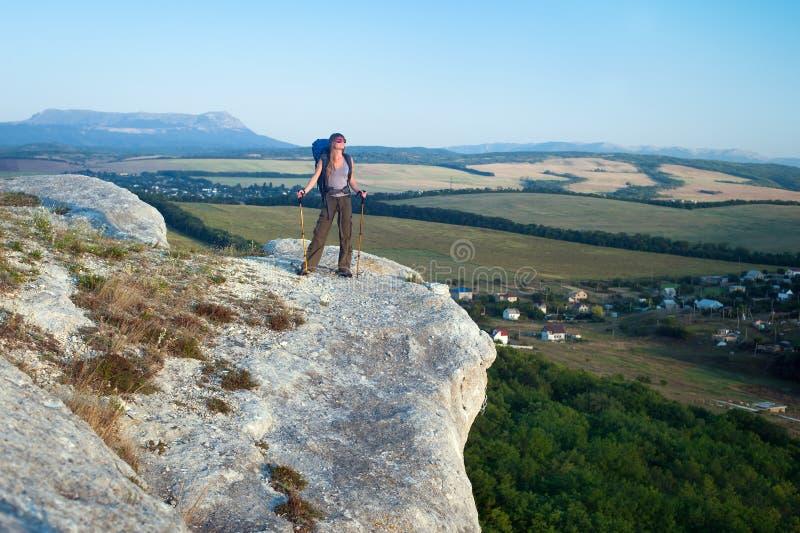 Усмехаясь молодая женщина стоя на верхней части горы стоковое фото rf