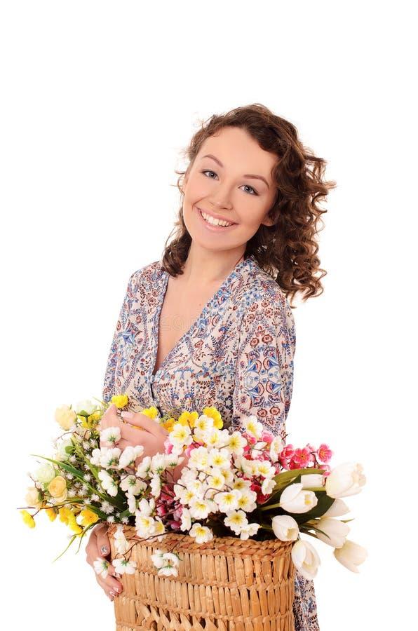 усмехаясь молодая женщина с корзиной цветков стоковое фото rf
