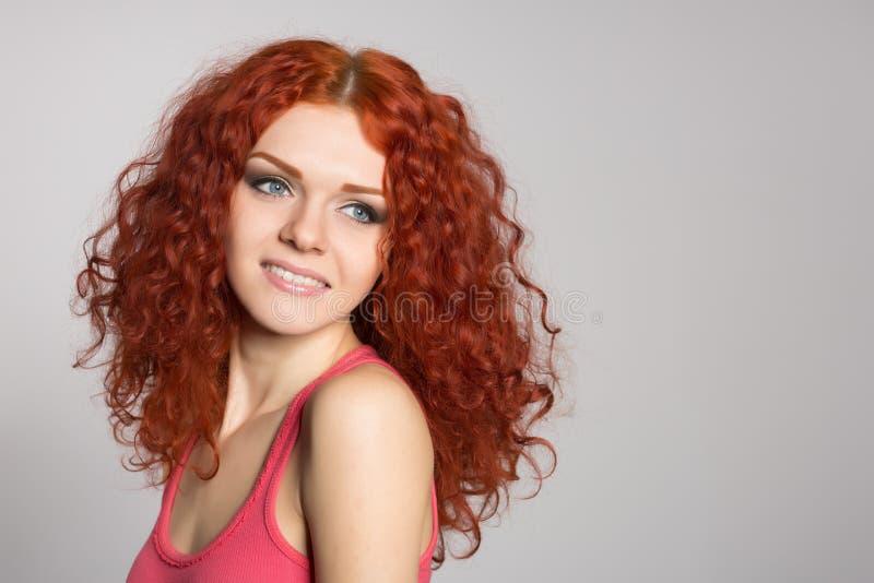 Усмехаясь молодая женщина с красными волосами на сером цвете стоковое фото