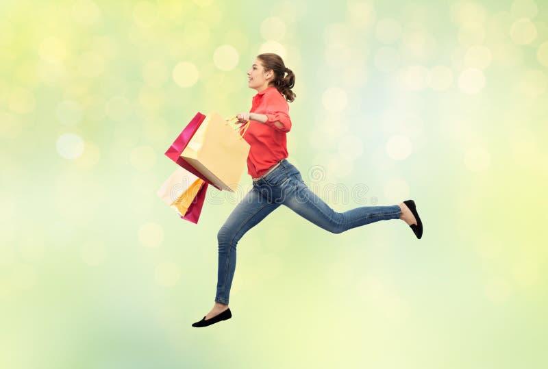 Усмехаясь молодая женщина с скакать хозяйственных сумок стоковое изображение