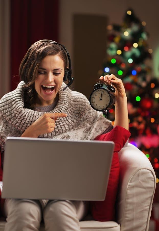 Усмехаясь молодая женщина указывая на часы пока имеющ видео- болтовню стоковые изображения