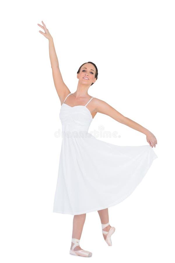 Усмехаясь молодой артист балета представляя с ее задней частью ноги стоковые фотографии rf