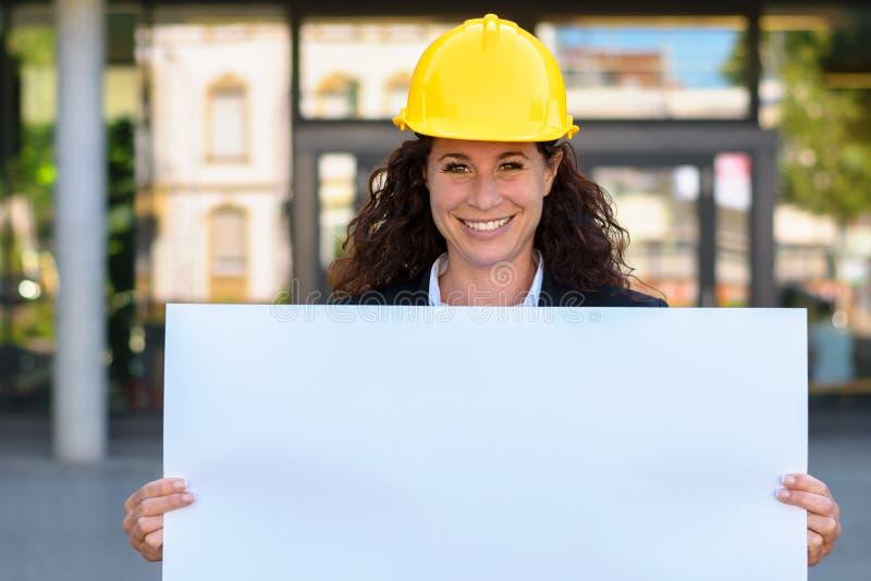 Усмехаясь молодой архитектор держа пустой знак стоковая фотография
