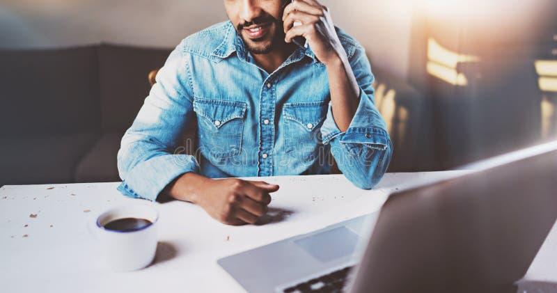 Усмехаясь молодой африканский человек говоря smartphone пока сидящ на деревянном столе его современный дом Концепция детенышей стоковые изображения rf