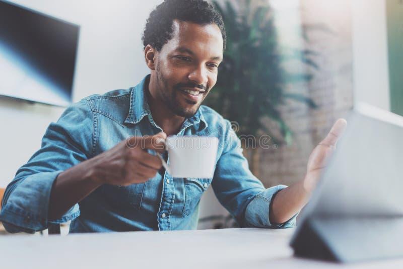 Усмехаясь молодой африканский человек делая видео- переговор через цифровую таблетку с семьей пока выпивающ черный кофе в солнечн стоковые фото