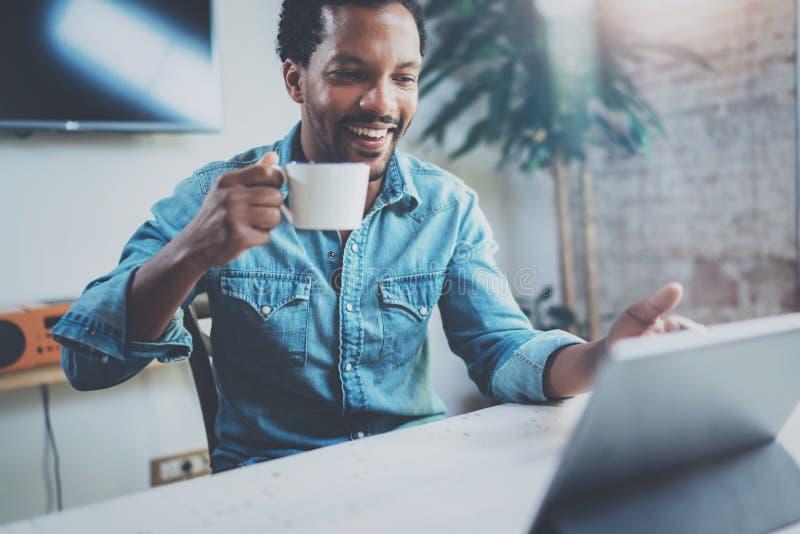 Усмехаясь молодой африканский человек делая видео- переговор через цифровую таблетку с партнерами пока выпивающ черный кофе внутр стоковые изображения