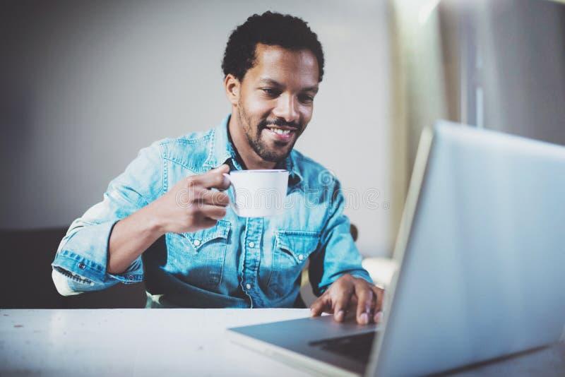 Усмехаясь молодой африканский человек делая видео- переговор через компьтер-книжку с партнерами пока выпивающ чай белой чашки чер стоковое изображение