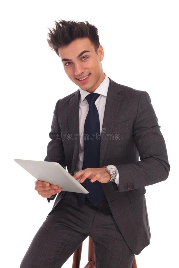 Усмехаясь молодой бизнесмен касаясь экрану его таблетки стоковое изображение
