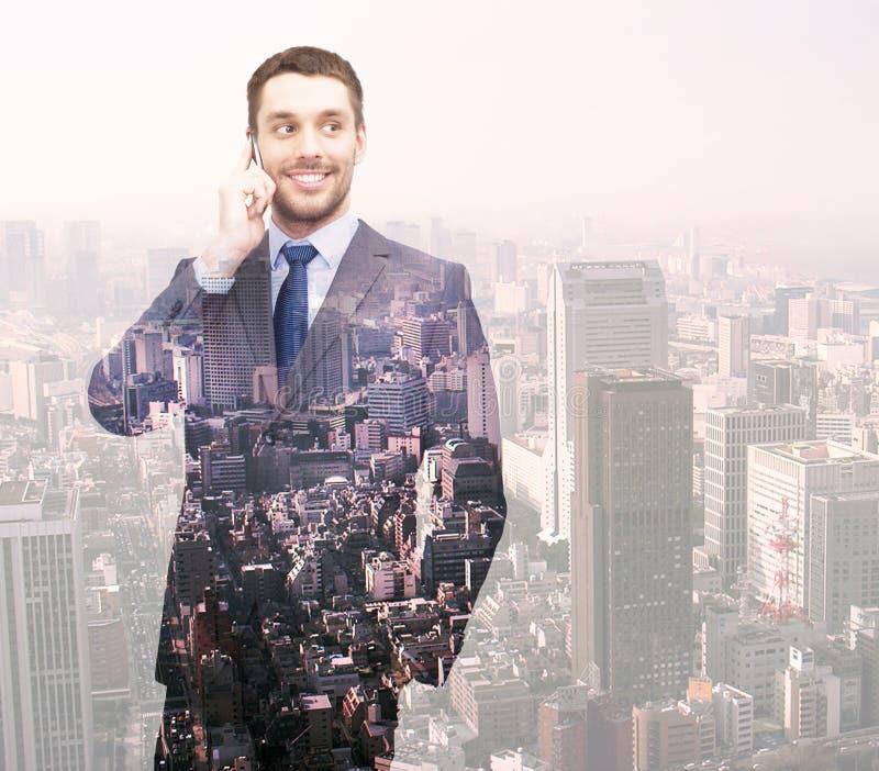 Усмехаясь молодой бизнесмен над предпосылкой города стоковая фотография rf