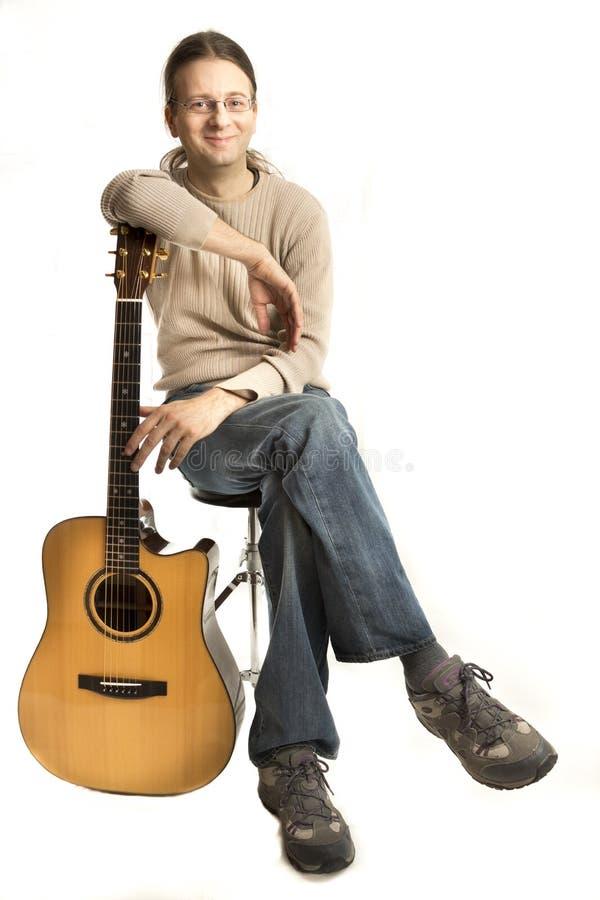 Усмехаясь молодой гитарист стоковое фото rf