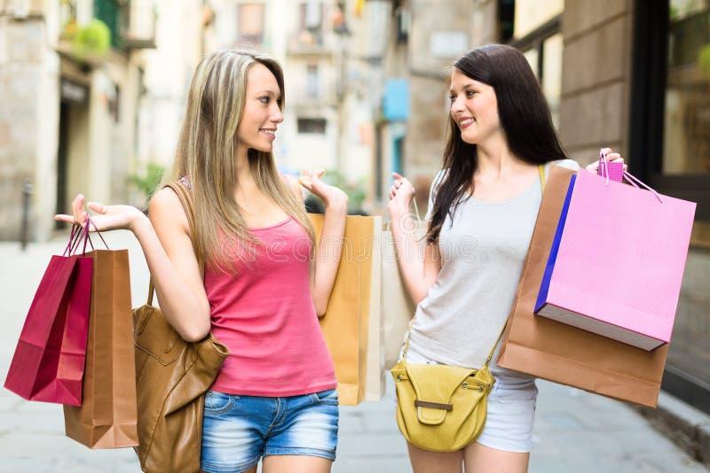 2 усмехаясь молодой женщины делая покупки стоковое фото rf