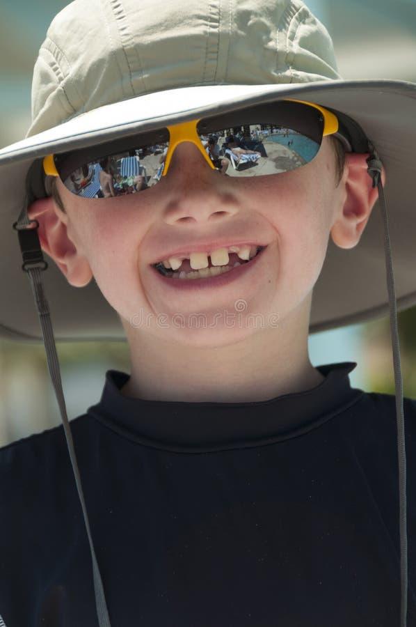 Усмехаясь молодой мальчик нося шляпу. стоковая фотография
