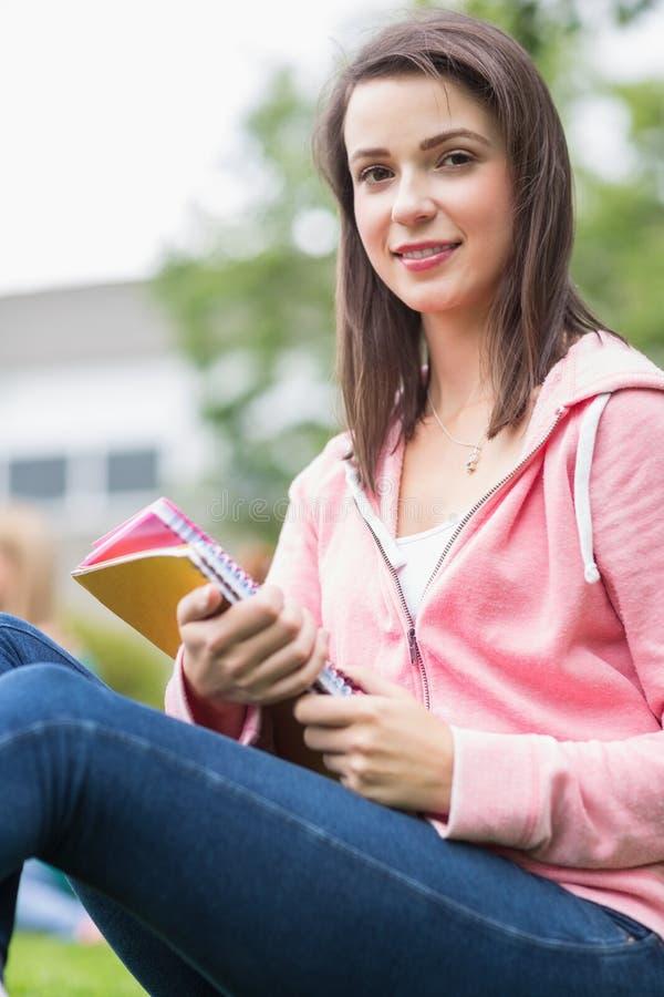 Усмехаясь молодой студент колледжа с книгами в парке стоковое изображение rf