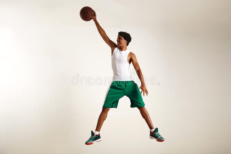 Усмехаясь молодой чернокожий человек достигая высоко для баскетбола стоковые изображения rf