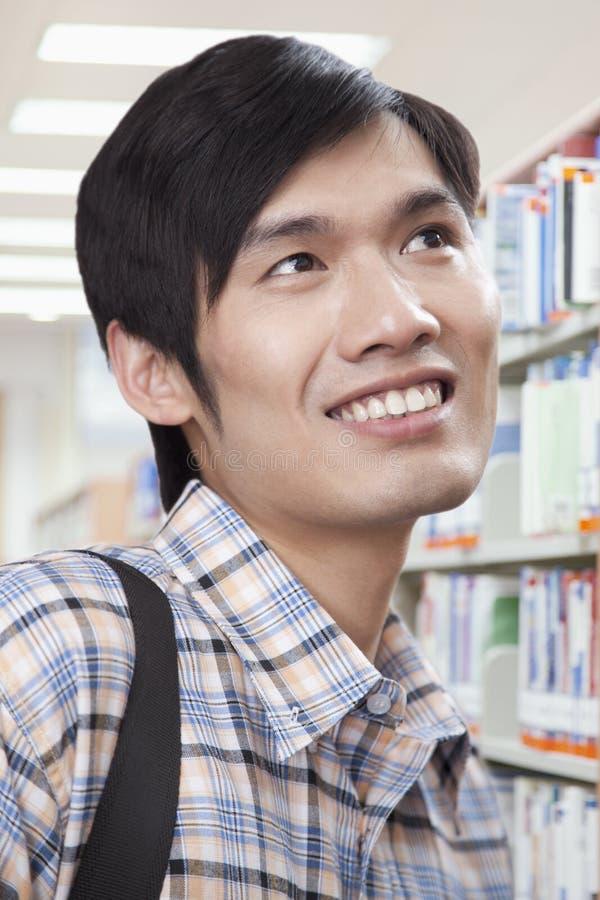 Усмехаясь молодой человек в библиотеке смотря прочь стоковое фото