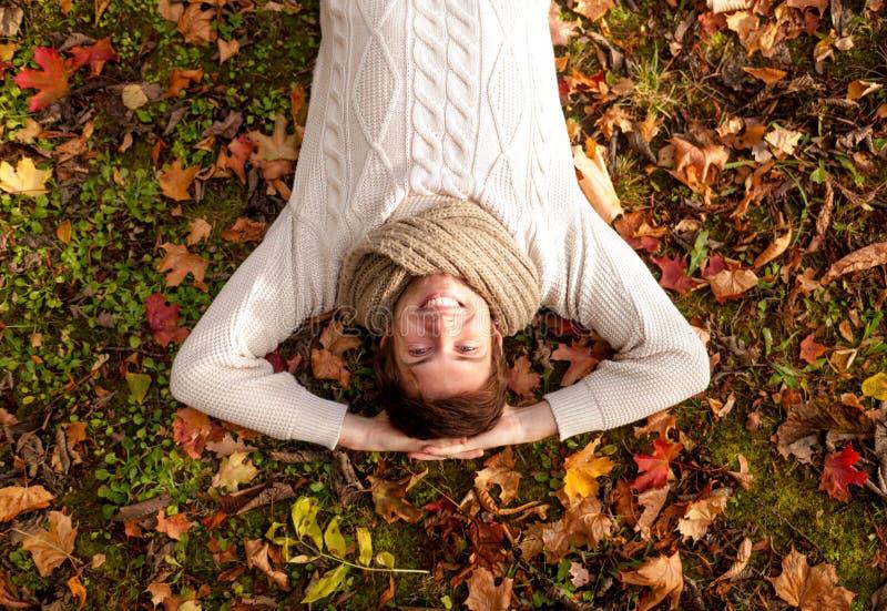 Усмехаясь молодой человек лежа на земле в парке осени стоковое изображение