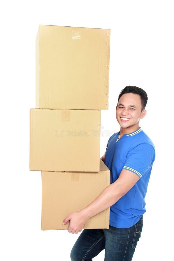 Усмехаясь молодой человек держа картонную коробку стоковая фотография rf