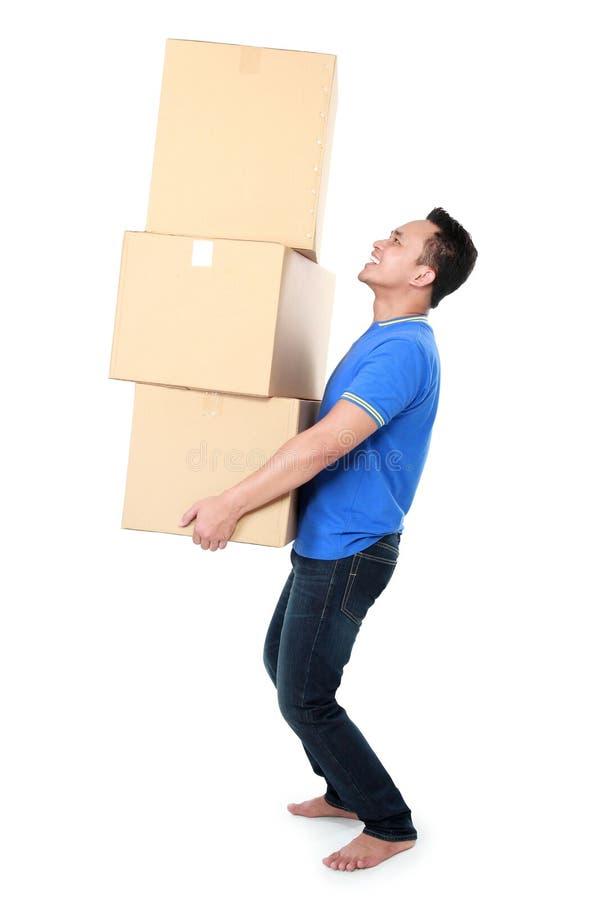 Усмехаясь молодой человек держа картонную коробку стоковые изображения rf
