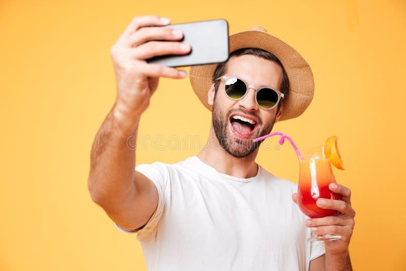 Усмехаясь молодой человек делает selfie телефоном держа коктеиль стоковое фото