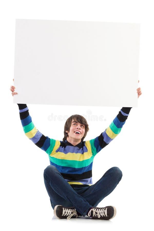 Усмехаясь молодой человек показывая пустой плакат стоковое фото