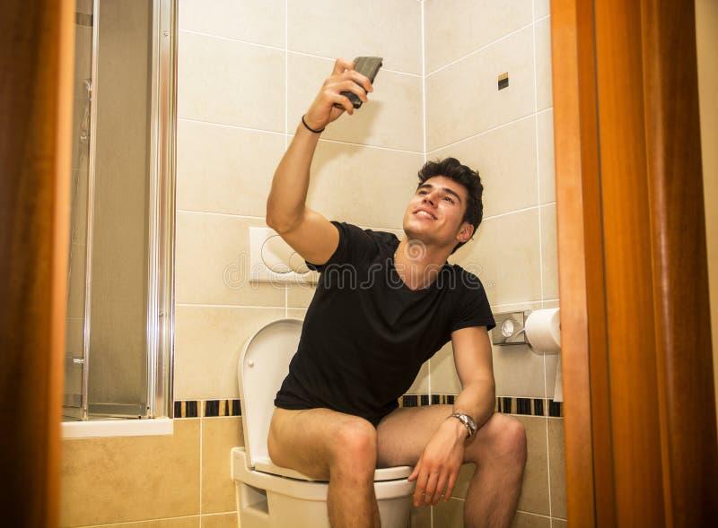 Усмехаясь молодой человек принимая selfie пока испражняющся стоковые изображения rf