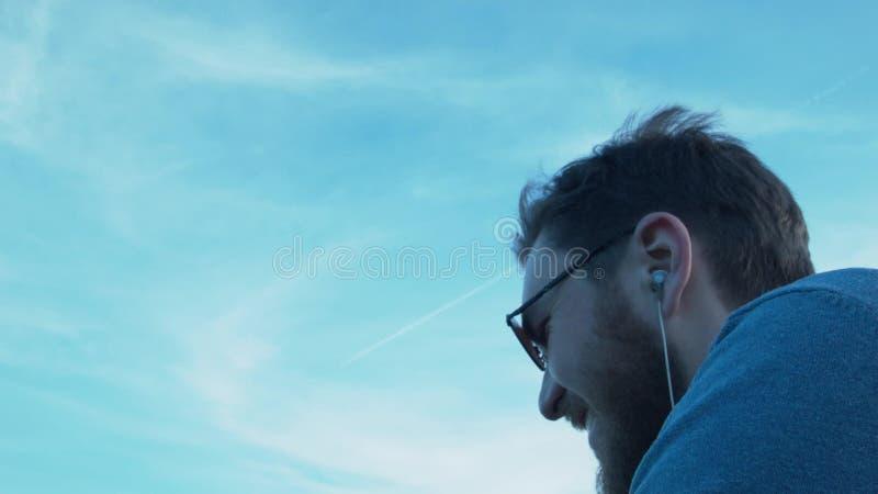 Усмехаясь молодой человек при наушники и стекла смотря небо на самолете красивые детеныши портрета человека видеоматериал