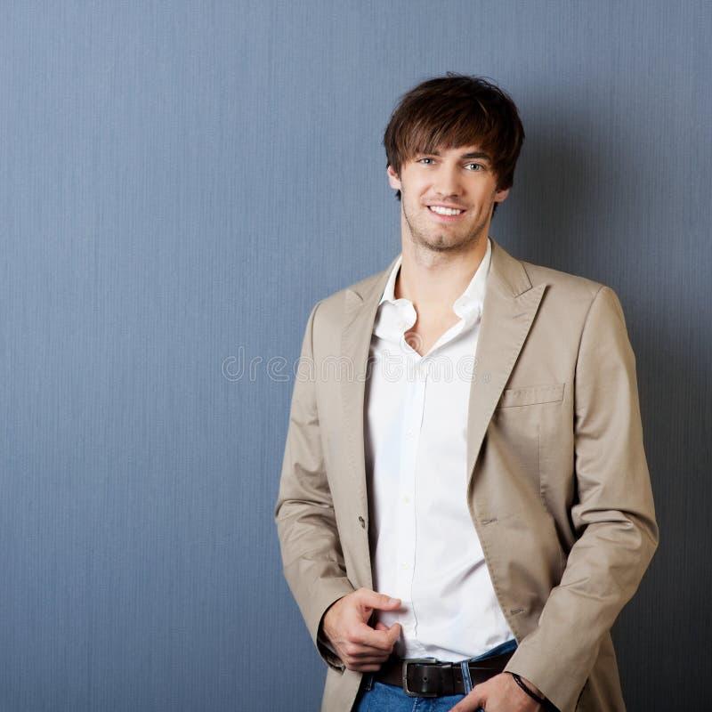 Усмехаясь молодой человек с курткой стоковая фотография rf