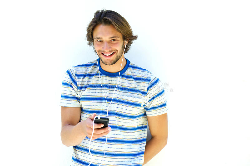 Усмехаясь молодой человек слушая к склонности музыки на белой стене стоковые фото