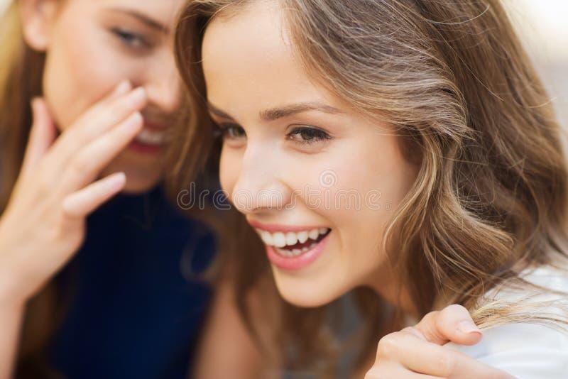 Усмехаясь молодые женщины злословя и шептать стоковое изображение