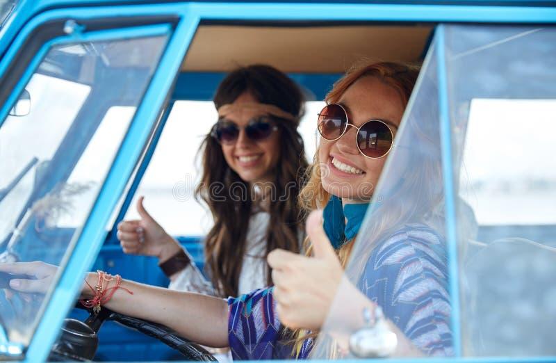 Усмехаясь молодые женщины hippie управляя автомобилем минифургона стоковая фотография