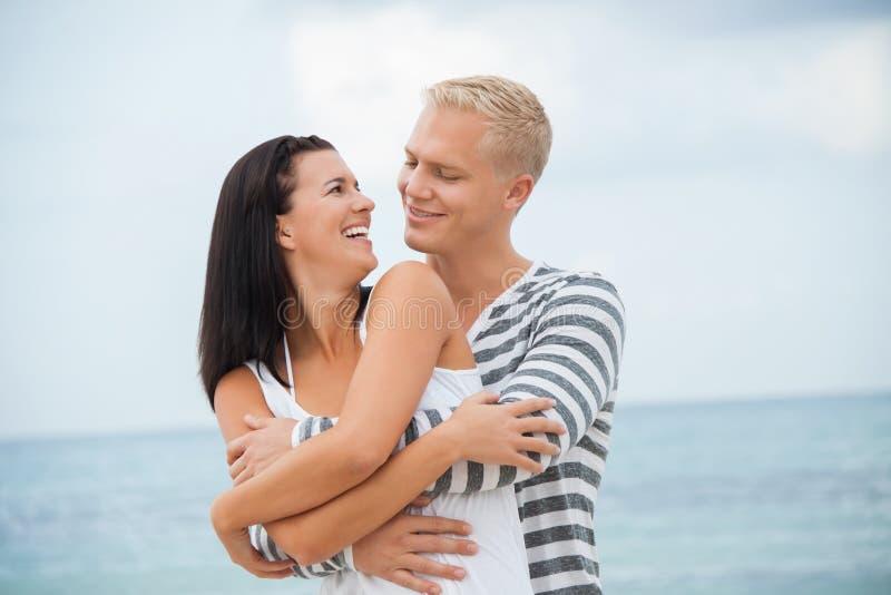 Усмехаясь молодые пары имея потеху в летнем отпуске стоковая фотография rf