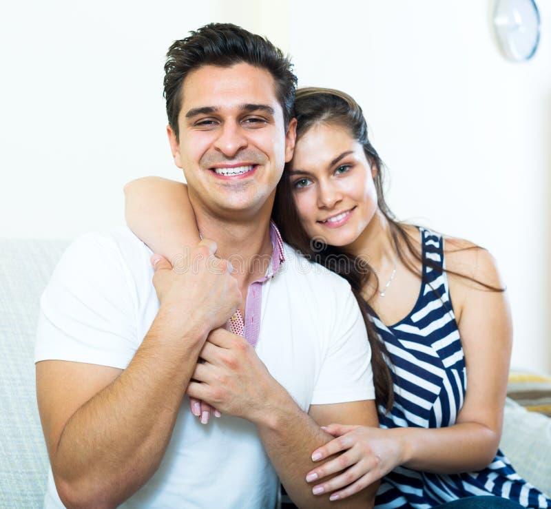 Усмехаясь молодые супруги представляя и обнимать стоковое фото