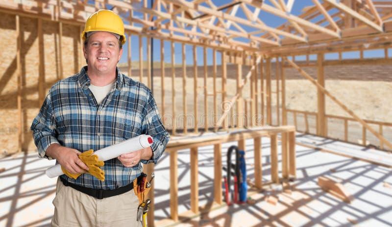 Усмехаясь мужской подрядчик при планы дома нося трудную шляпу внутри нового Hou стоковое фото
