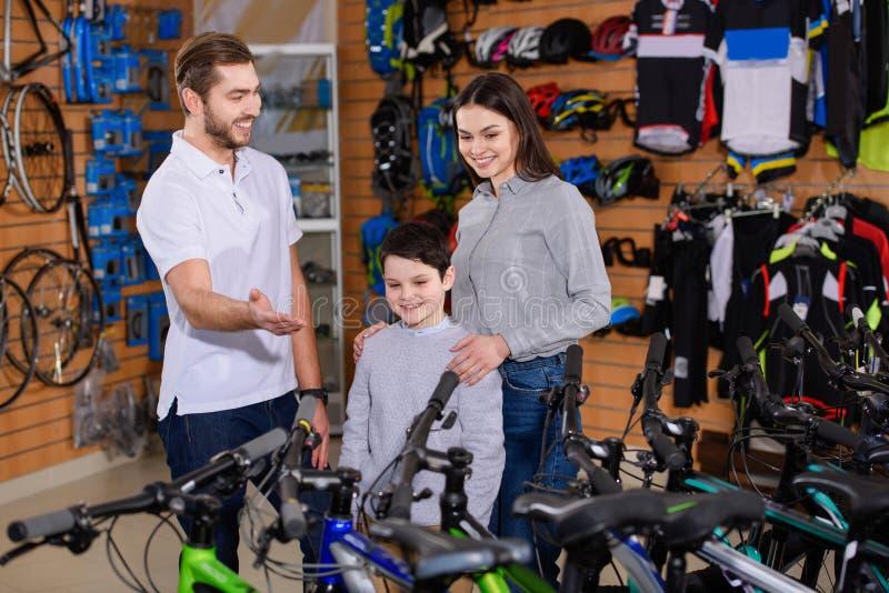 усмехаясь мужской продавец показывая велосипеды к молодой матери с сыном стоковое изображение rf