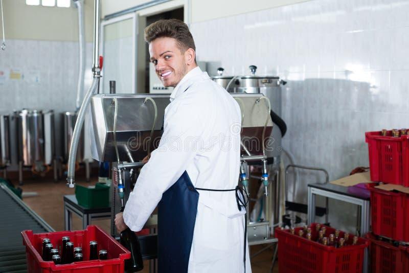 Усмехаясь мужской работник используя машину на фабрике игристого вина стоковая фотография rf